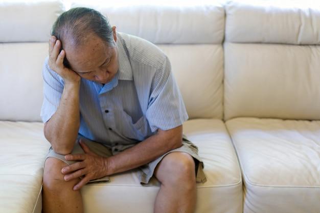 Feche acima da opinião o homem sênior asiático que sofre da dor de cabeça.