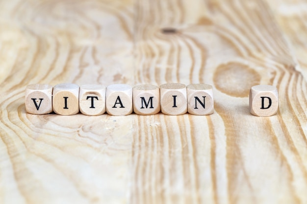 Feche acima da palavra da vitamina d feita das letras de madeira na tabela, conceito da saúde