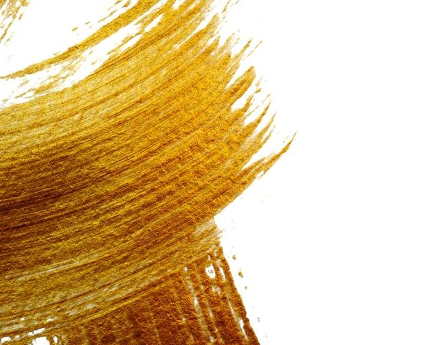Feche acima da parede abstrata de ouro com pincel de tinta acrílica