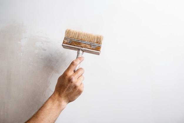 Feche acima da parede da pintura da mão com escova.