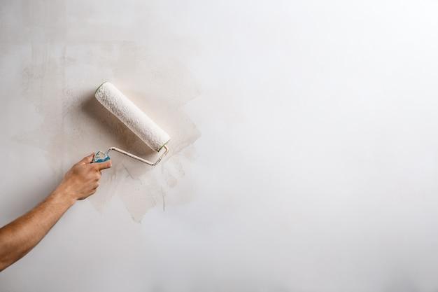 Feche acima da parede da pintura da mão com rolo.
