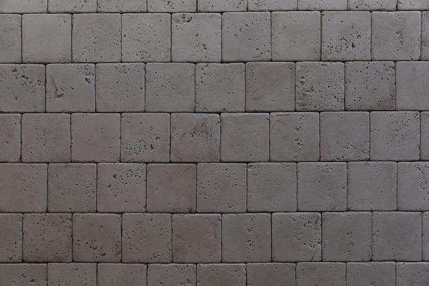 Feche acima da parede de tijolo quadrado de grafite