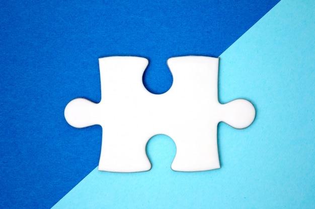 Feche acima da parte branca do enigma sobre um fundo do azul da geometria. estilo minimalista. lay plana.