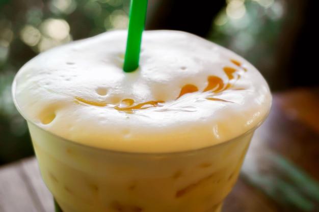 Feche acima da parte superior do gelo latte e veja a arte do latte na espuma do leite na licença verde.