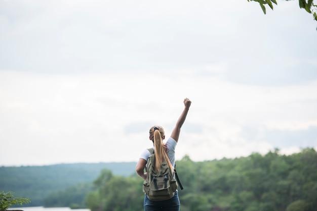 Feche acima da parte traseira da menina do turista com os braços que aumentam feliz com natureza perto do lago. conceito de viagens.