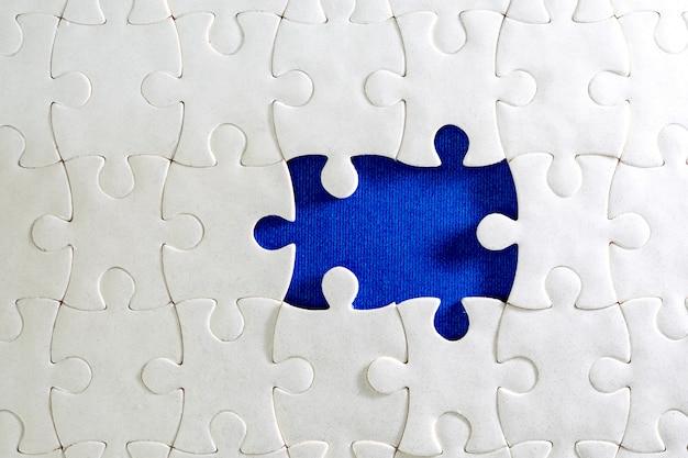 Feche acima da peça do quebra-cabeça branca, conceito de conclusão do desafio de negócios com trabalho em equipe