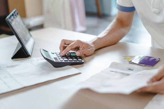 Feche acima da pessoa que calcula a despesa mensal e a dívida do cartão de crédito.