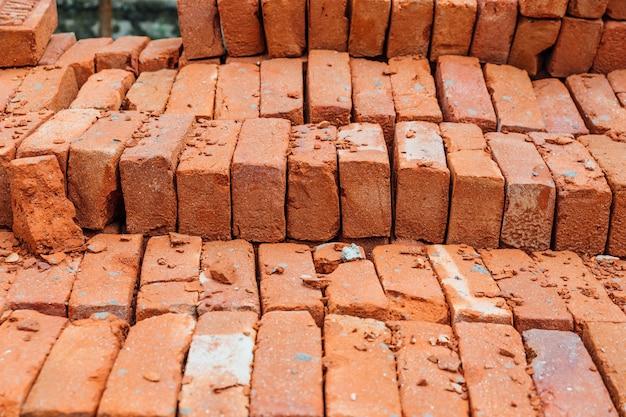 Feche acima da pilha da textura do tijolo vermelho com musgo em alguns tijolos.