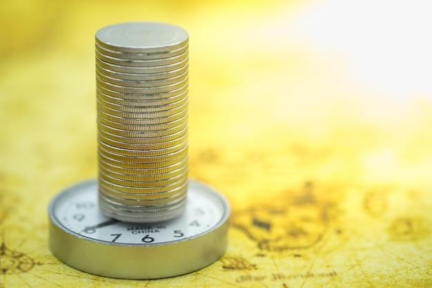 Feche acima da pilha das moedas de prata no relógio redondo e no mapa do mundo.
