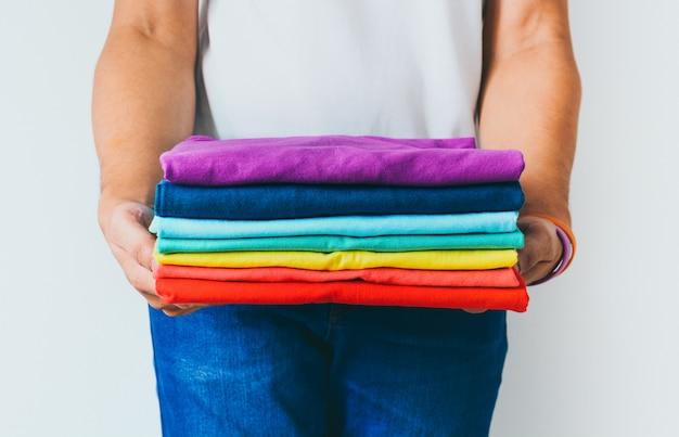 Feche acima da pilha de camisetas multicoloridas dobradas nas mãos