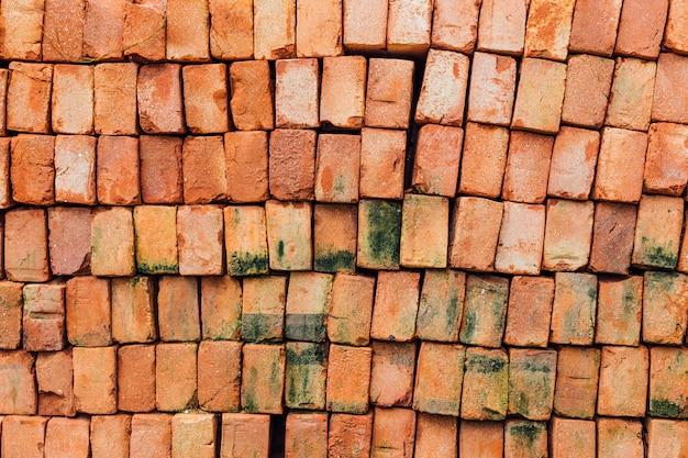 Feche acima da pilha de textura de tijolo vermelho com musgo em alguns tijolos