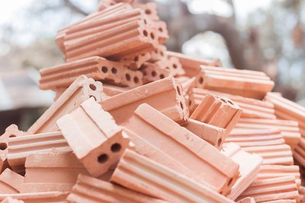 Feche acima da pilha de tijolos vermelhos para a construção.