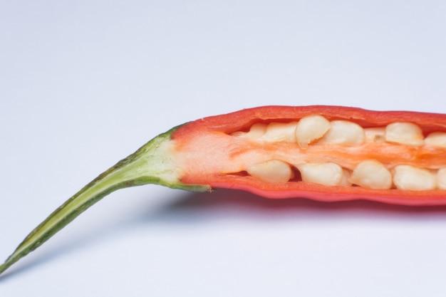 Feche acima da pimenta vermelha cortada isolada no branco.