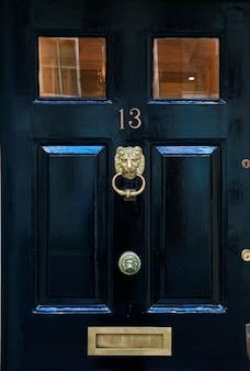 Feche acima da porta de madeira com aldrava de bronze antiquado, e entalhe da letra