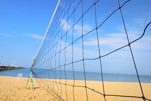 Feche acima da rede de voleibol com praia do mar e o céu azul no verão. natureza, ao ar livre e conceito de esporte.