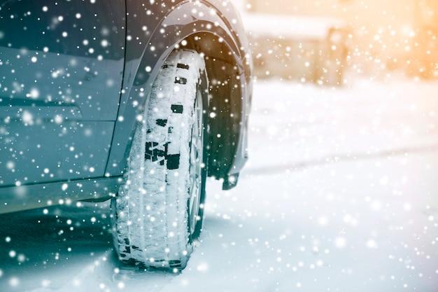 Feche acima da roda de carro do detalhe com o protetor preto novo do pneu de borracha na estrada coberto de neve do inverno. transporte e conceito de segurança.