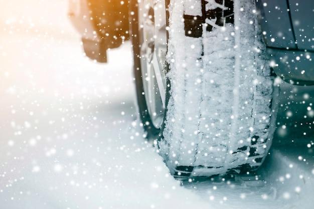 Feche acima da roda de carro do detalhe com o protetor preto novo do pneu de borracha na estrada coberto de neve do inverno. transporte e segurança.