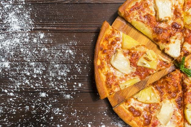 Feche acima da saborosa pizza fatiada exótica havaiana quente com fatias de abacaxi doce, carne de frango e queijo. vista superior, comida italiana nacional. fundo de madeira marrom escuro, mesa com farinha polvilhada