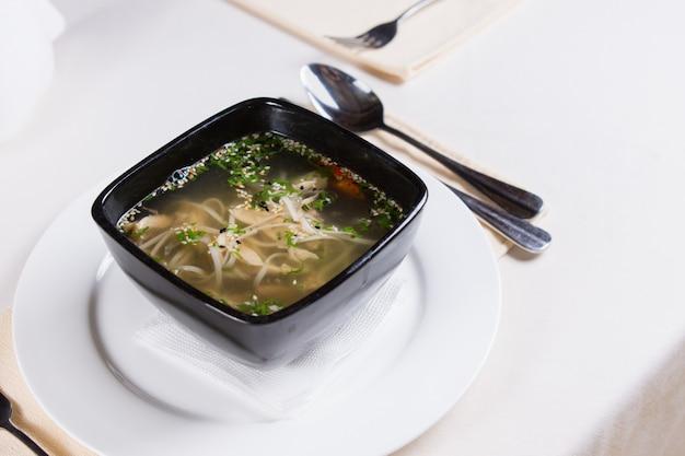 Feche acima da saborosa sopa de carne picante quente na tigela preta acima do prato redondo branco pedido no restaurante.