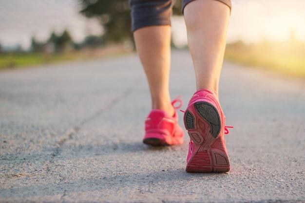 Feche acima da sapatilha dos pés do corredor da mulher do atleta na estrada rural ao executar o exercício