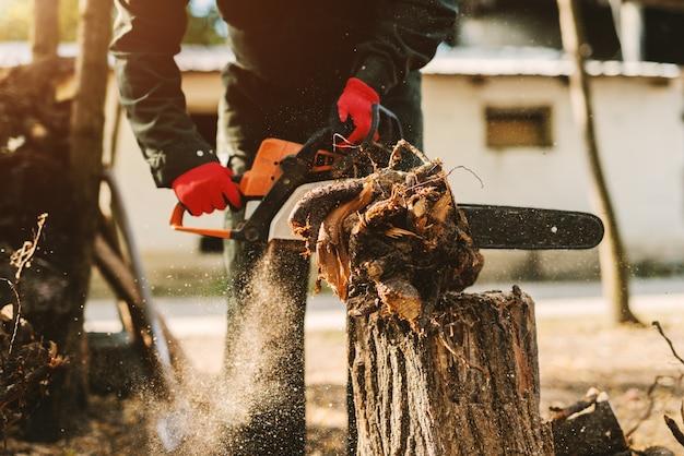 Feche acima da serra elétrica nas mãos do homem que cortam grande parte da árvore. homem em madeira de corte uniforme protetor lá fora.