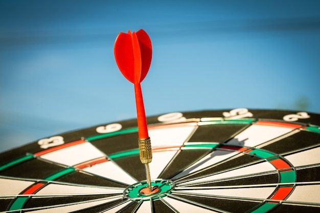 Feche acima da seta vermelha do dardo que acerta no centro do alvo do alvo de dardos, objetivo do negócio ou conceito de sucesso do alvo.