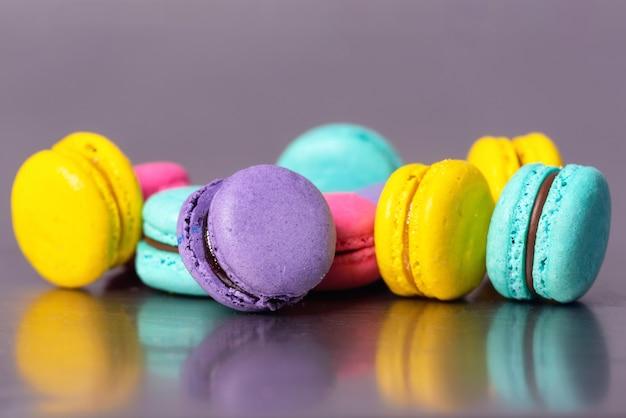 Feche acima da sobremesa colorida dos macarons no fundo roxo.