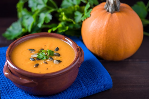 Feche acima da sopa de abóbora brilhante em uma bacia com salsa, azeite e sementes de abóbora em um fundo escuro de madeira.