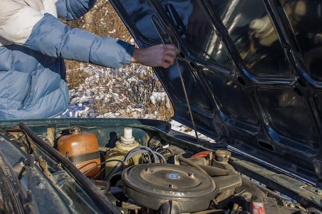 Feche acima da sujeira no detalhe de motor de automóveis velho na garagem.