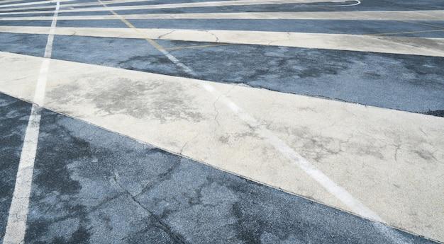 Feche acima da superfície da estrada de asfalto com faixa de tráfego branco