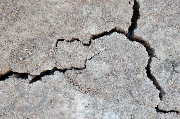 Feche acima da superfície rachada seca do solo.