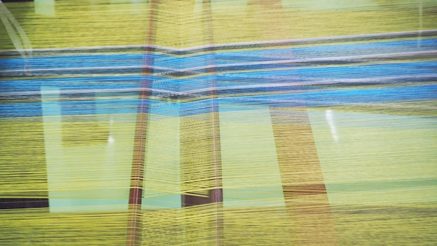 Feche acima da tecelagem tailandesa da seda em um tear tradicional. feche a linha de seda tailandesa. fabricação de seda tailandesa.