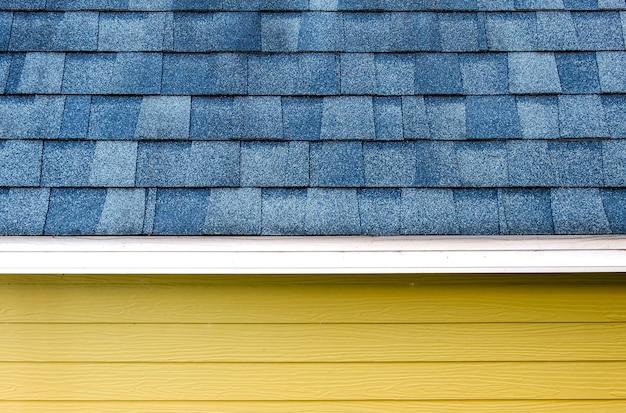 Feche acima da telha da escala do telhado e da parede de madeira da prancha, fundo da textura.