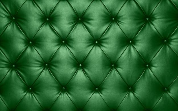 Feche acima da textura do fundo de couro genuíno capitone verde escuro, estofamento de móveis em estilo retrô chesterfield com padrão de diamante profundo e botões