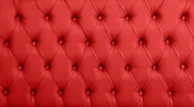 Feche acima da textura do fundo de couro genuíno capitone vermelho escarlate, estofamento de móveis de tufos macios estilo chesterfield retrô com padrão de diamante profundo e botões