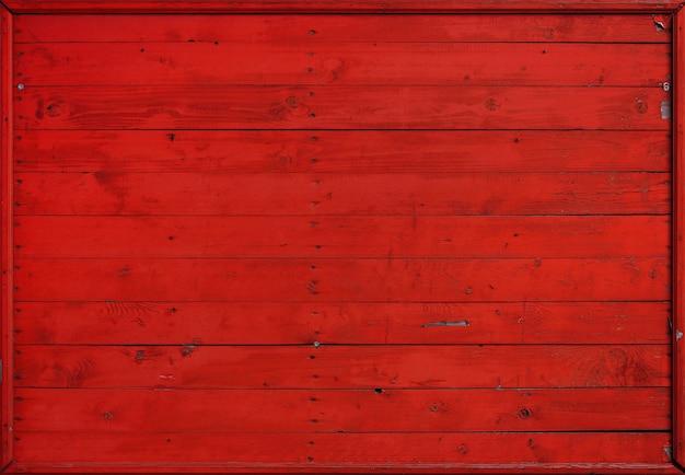 Feche acima da textura do fundo de pranchas de madeira pintadas resistidas vintage vermelhas, painel de parede de estilo rústico