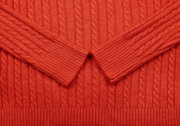 Feche acima da textura do fundo do suéter de malha de lã tricotada com fio vermelho com padrão de trança