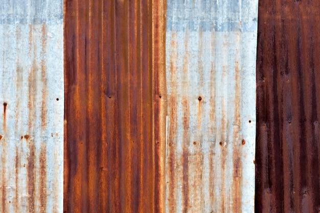 Feche acima da textura oxidada da folha de metal do ferro ondulado.
