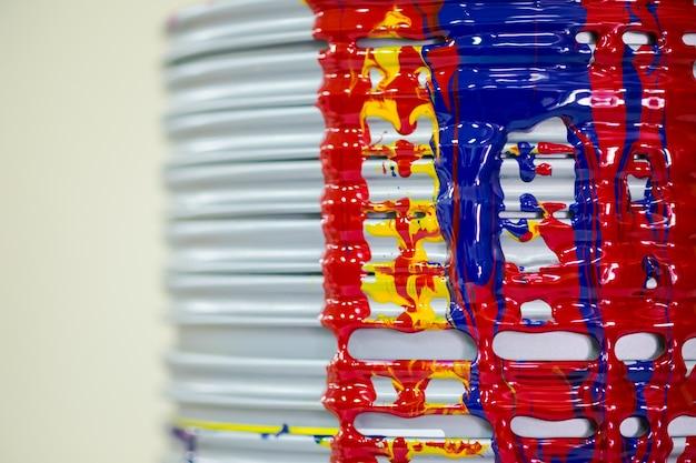 Feche acima da tinta da indústria de impressão pingando na borda das latas.