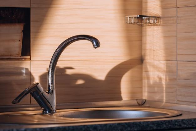 Feche acima da torneira de metal prata velha em uma cozinha no sol