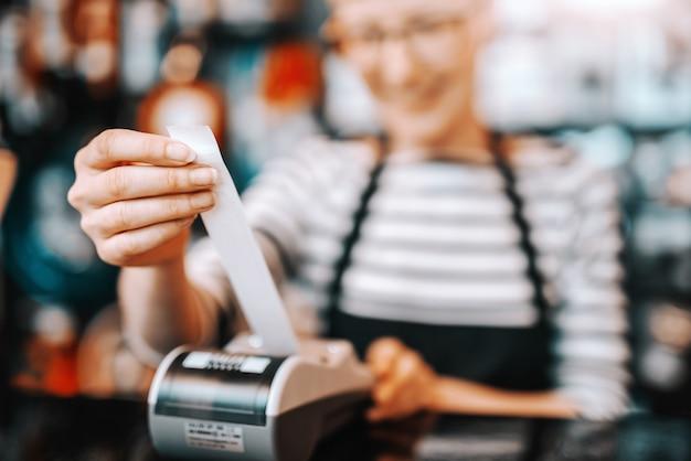 Feche acima da trabalhadora caucasiana sorridente com cabelo loiro curto e óculos usando a caixa registradora em pé na loja de bicicletas.
