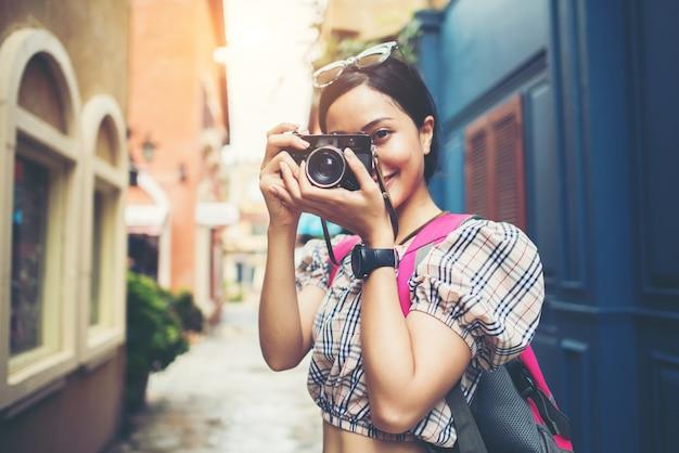 Feche acima da trouxa nova da mulher do moderno que viaja tomando a foto com sua câmera em urbano.