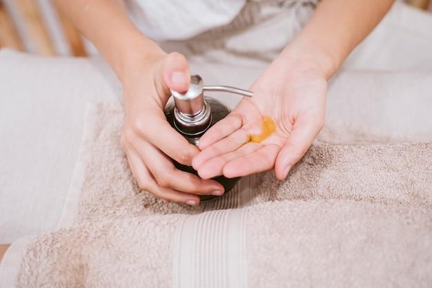Feche acima da vista da mulher profissional fisioterapeuta usando óleo pronto para dar uma massagem na clínica. conceito de fisioterapia e cuidados com o corpo