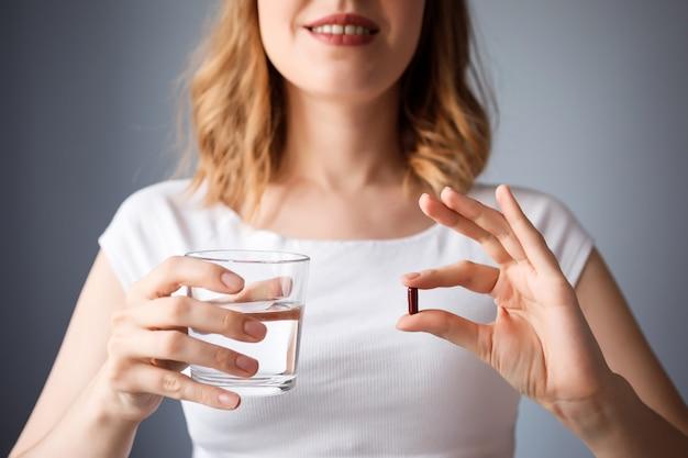 Feche acima da vista da mulher segurando o copo de água e um comprimido. tratamento de saúde, medicação.