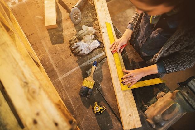 Feche acima da vista da mulher séria profissional carpinteiro profissional focada segurando a régua e lápis ao fazer marcas na madeira à mesa na oficina de tecidos.