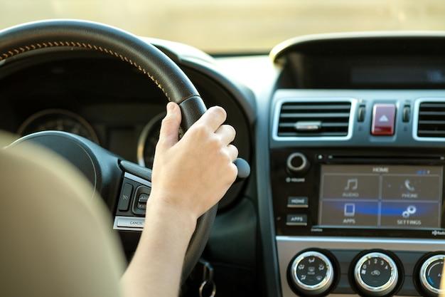 Feche acima da vista das mãos da mulher segurando o volante dirigindo um carro na rua da cidade em dia ensolarado.