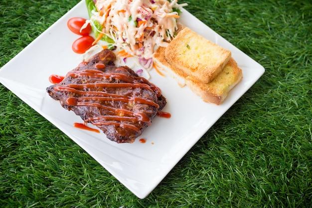 Feche acima da vista de reforços do assado da carne de porco com o molho de assado que serviu com salada do pão e do vegetal de alho.