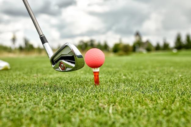 Feche acima da vista de tacos e bolas de golfe em um gramado verde em um belo campo de golfe com sol da manhã.