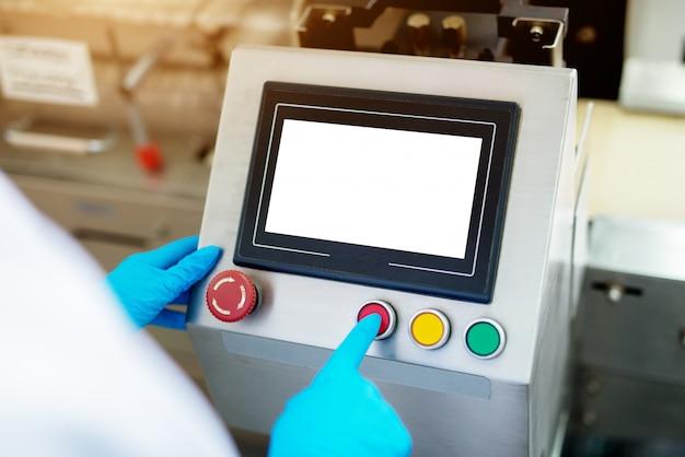 Feche acima da vista de um painel de controle da linha de produção da indústria com botões vermelhos de amarelos e verdes, sendo pressionados por um trabalhador em um pano estéril.