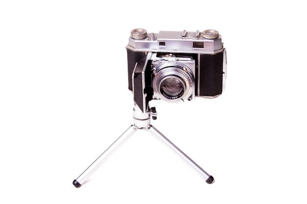 Feche acima da vista de uma câmera fotográfica do vintage retro isolada em um fundo branco.
